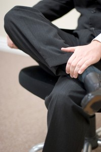 Businessman sits in his office and crosses his legs with his hand on his leg